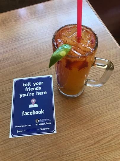 orange alcoholic drink with a lime wedge, and a facebook advertisement on the the table next to it