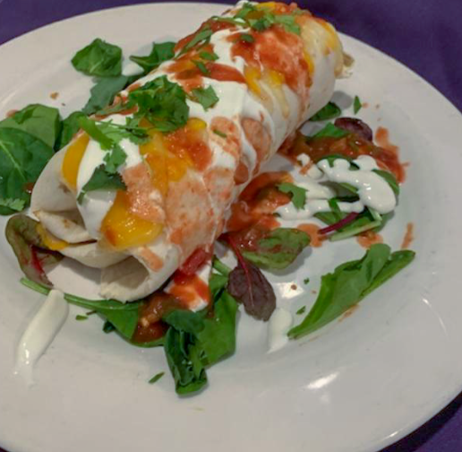 Burrito drizzled with white sauce on bed of fresh basil and herbs