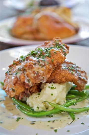 Fried chicken over mashed potatoes and green beans