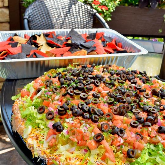 pizza with olives, tomatoes, and lettuce