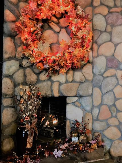 fire place decorated with leaves and a wreath