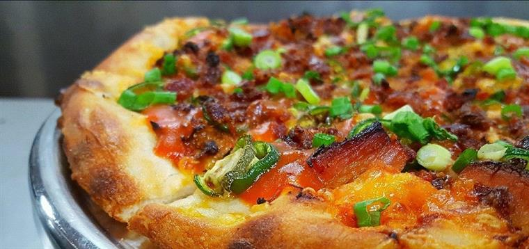 Pizza with a variety of toppings including onions and bacon.
