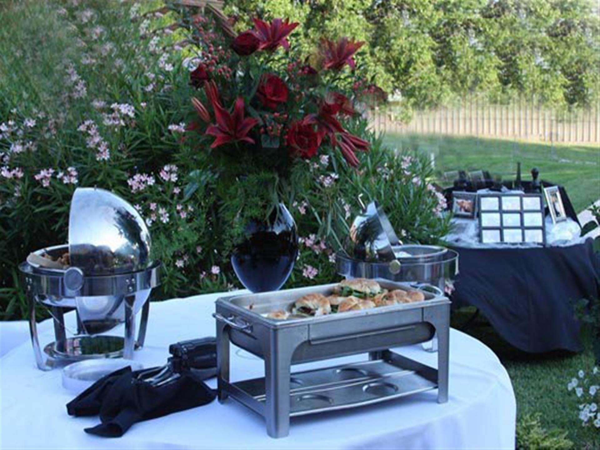 Catering sternos with sandwiches on outdoor table with white cloth