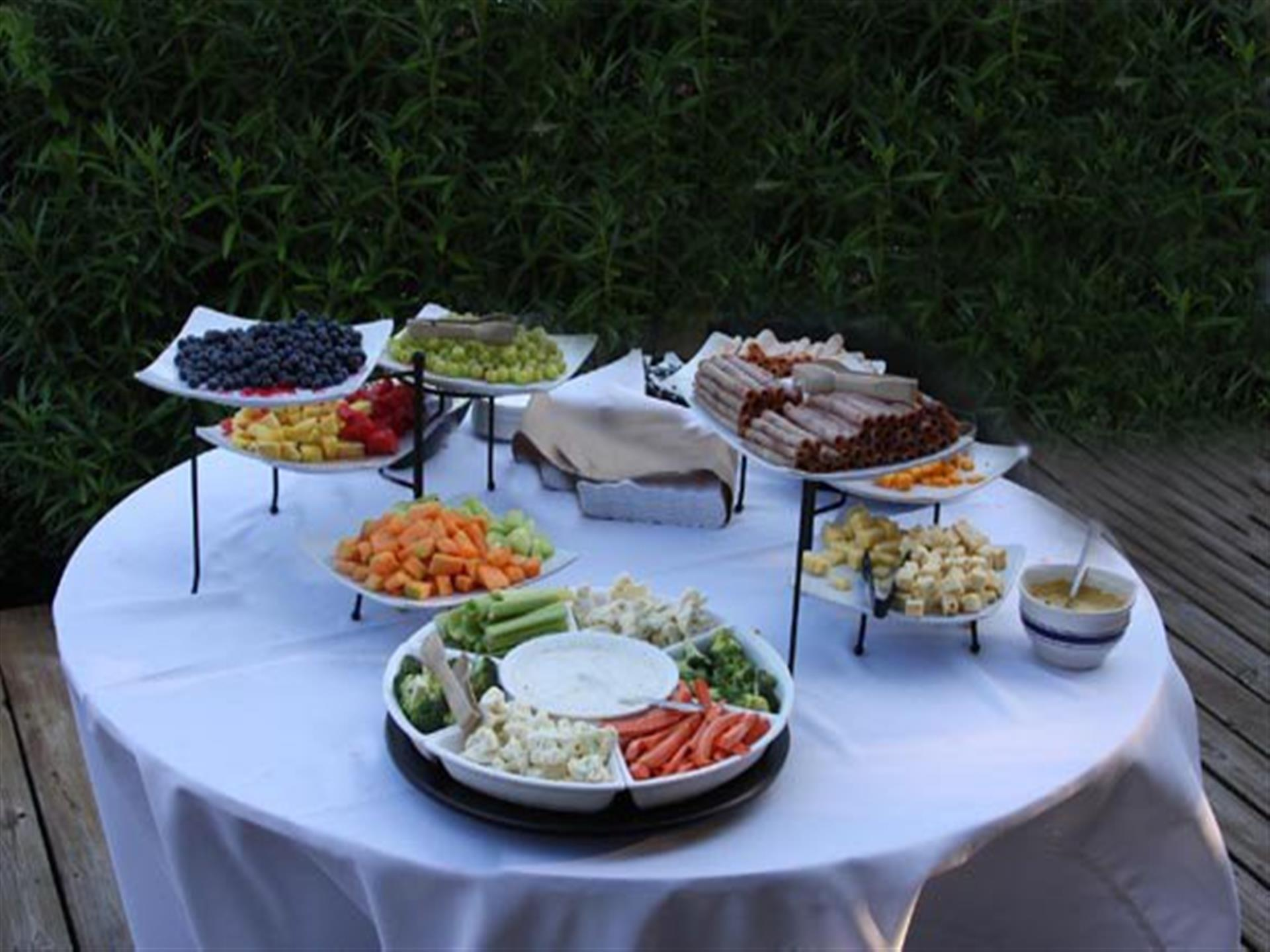 Display of fruits, vegetables, cold cuts on outdoor table with white cloth