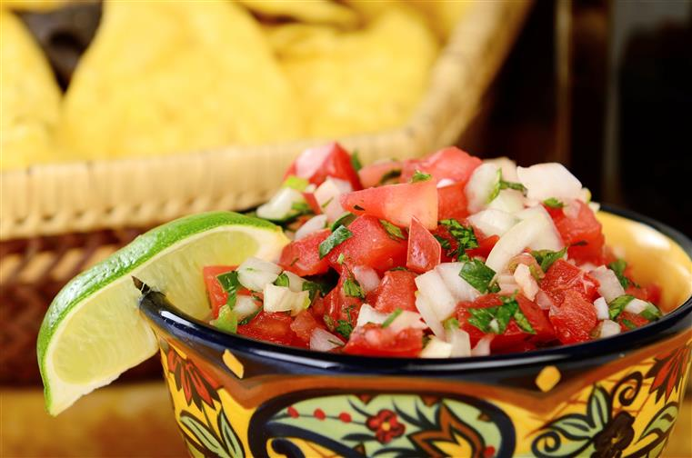 bowl of pico de gallo with a lime wedge