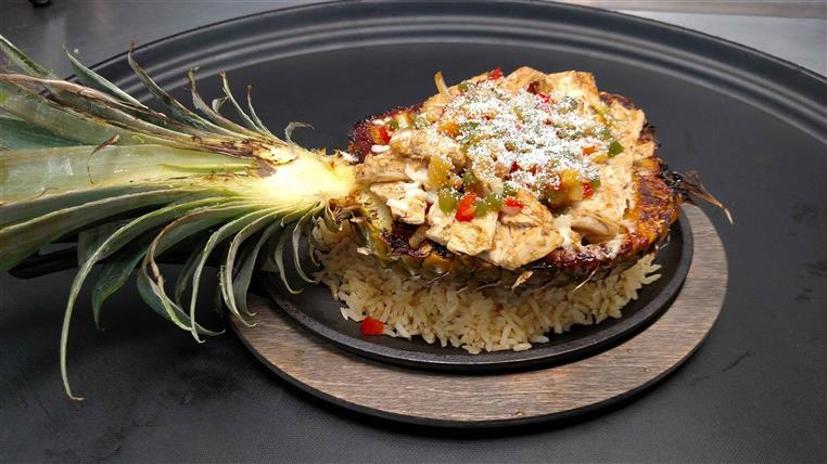 pineapple over a bed of rice topped with chicken, cheese, and peppers
