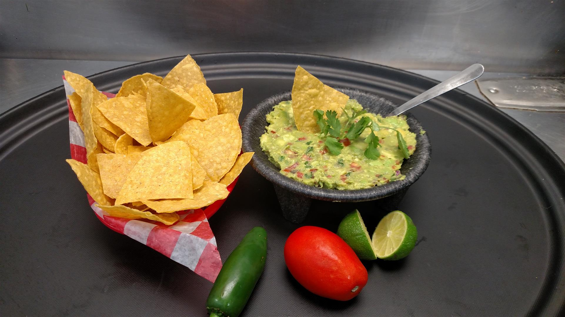 tray with bowl of guacamole and a basket of chips with a tomato, lime, and pepper on the side