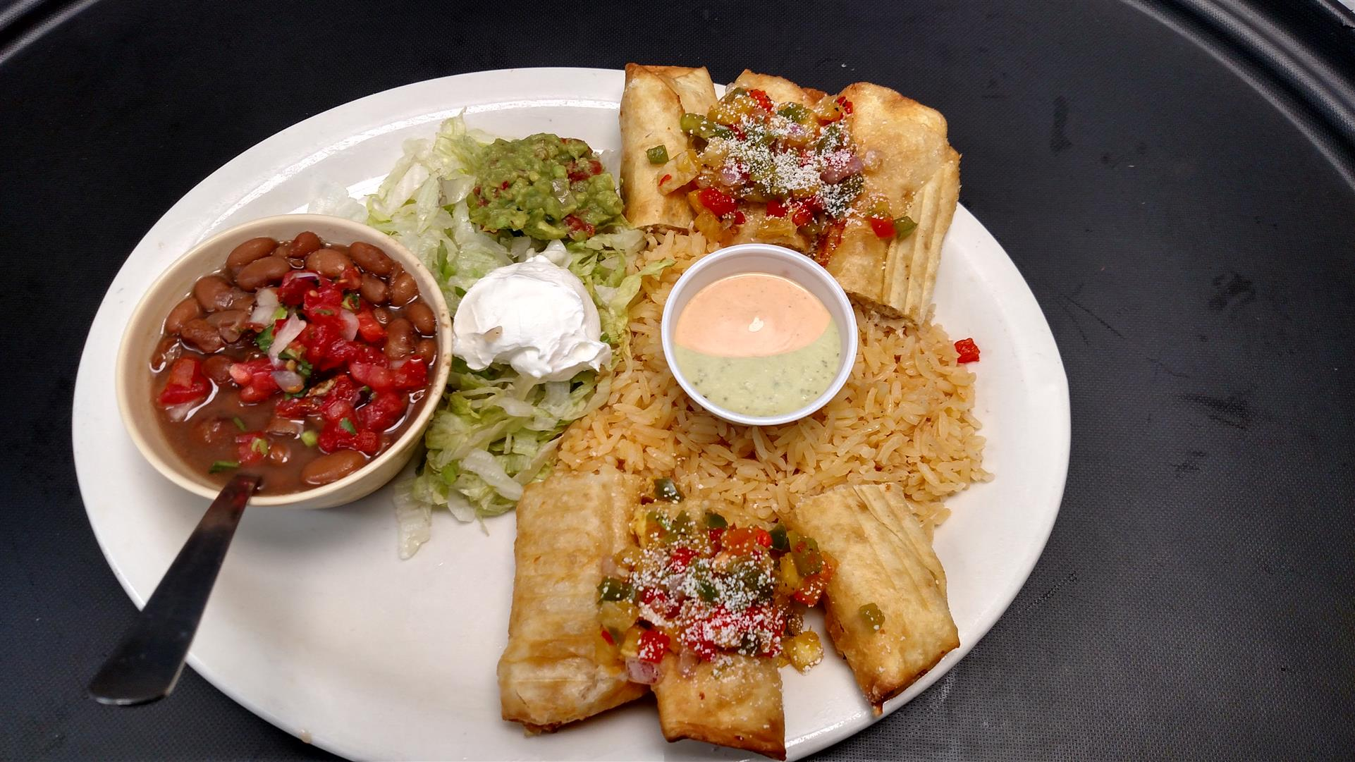 Chimichangas filled with beans, cheese, pico de gallo and deep-fried. Topped with salsa and cheese. Served with sour cream and rice on the side