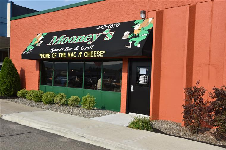 "outside of the storefront with the mooney's logo & ""Home of the mac n' cheese"""