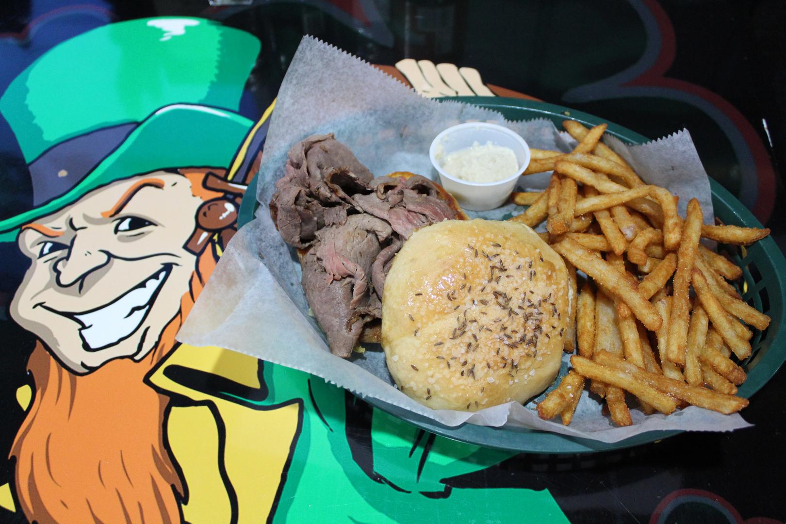 roast beef on a roll with a side of french fries on a table with a picture of a leprechaun